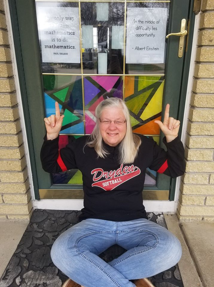 Mrs. Logan sitting in front of her classroom door